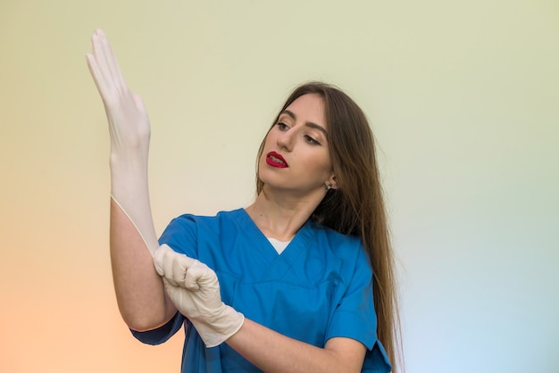 Belle femme médecin mettant un gant de protection en caoutchouc