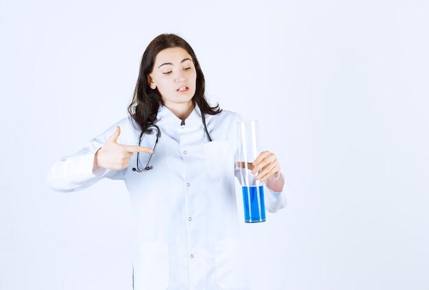 Une belle femme médecin pointe le tube à essai tout en tenant le stéthoscope autour de son cou
