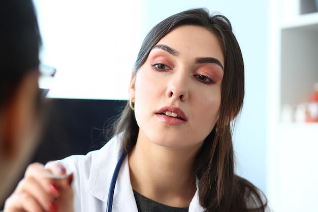 Belle femme médecin souriant parler avec le patient