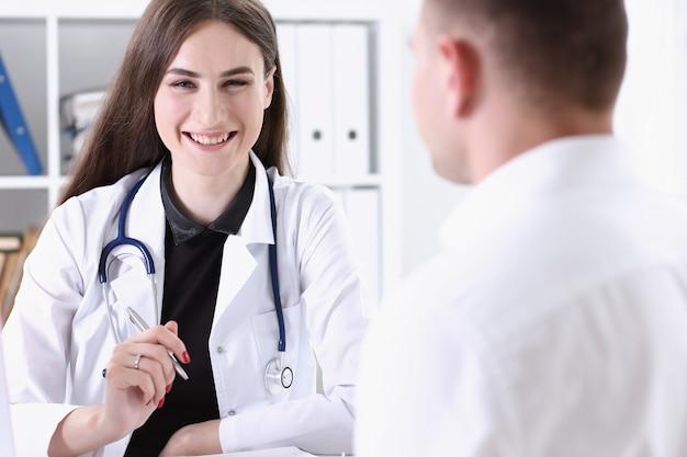 Belle femme médecin souriant tenir le stylo argent