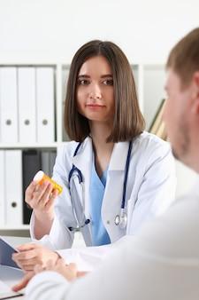 Belle femme médecin souriante tenir dans le pot de pilules d'armes et le donner au portrait du patient