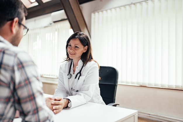 Belle femme médecin tenant par la main du patient.