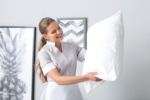 Belle femme de ménage avec oreiller moelleux dans la chambre