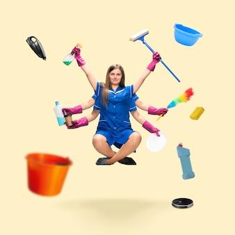 Belle femme de ménage à plusieurs bras en lévitation isolée sur fond de studio jaune avec équipement