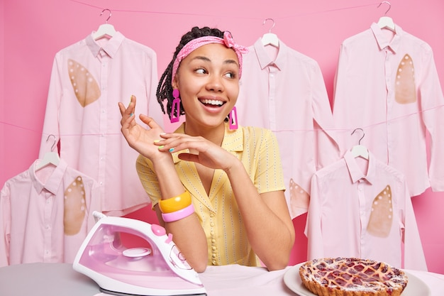 Belle femme de ménage rêveuse à la peau foncée regarde de côté, sourit joyeusement, fait des travaux ménagers et des poses de lessive près d'une planche à repasser avec une tarte au fer électrique qui travaille dur à la maison