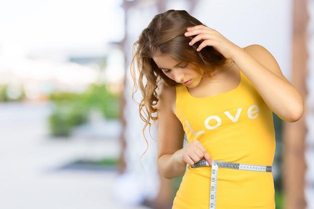Belle femme mesurant sa taille avec un ruban à mesurer