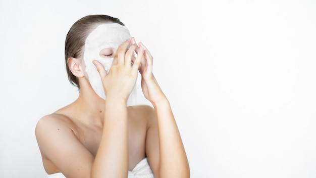 Belle femme met un masque cosmétique sur son visage