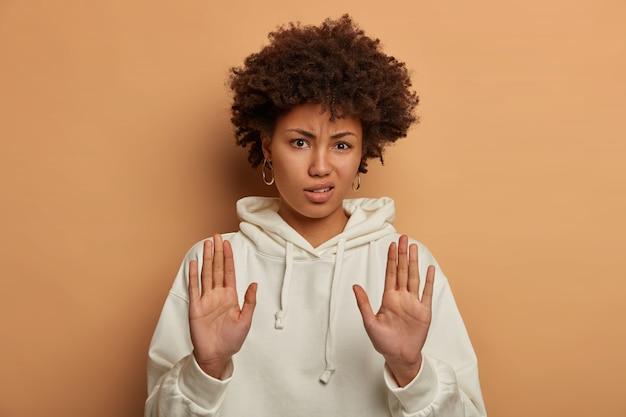 Belle femme millénaire mécontentement tire les mains vers la caméra, fait un geste d'arrêt ou d'avertissement, porte un sweat à capuche blanc