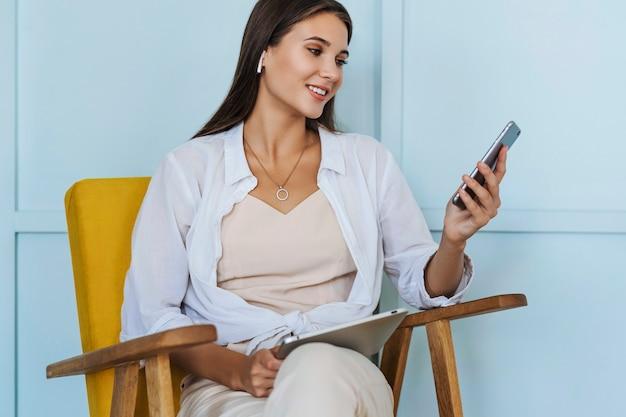 Belle femme millénaire travaille à la maison, assise sur un fauteuil jaune, à l'aide d'un smartphone, écrit des messages, partage des photos