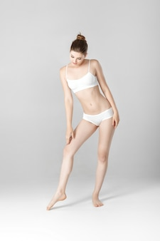 Belle femme mince avec un corps parfait en lingerie blanche sur fond gris