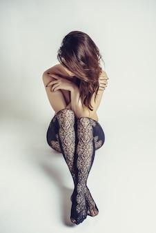 Belle femme mince posant dans des sous-vêtements séduisants et des bas sur fond isolé.