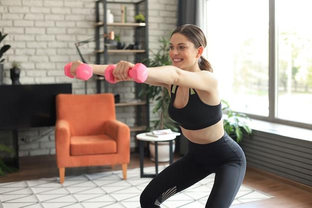 Belle femme mince de remise en forme s'accroupit avec des haltères. sport, mode de vie sain. la fille fait du sport à la maison.