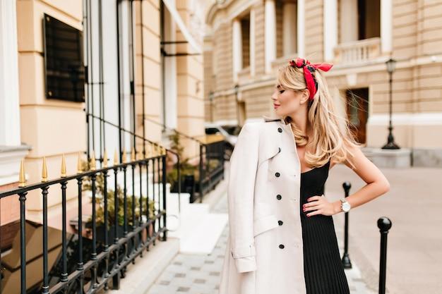 Belle femme mince en robe noire posant avec plaisir sur la vieille rue étroite