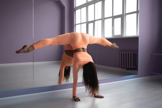 Belle femme mince en salopette de sport faisant du yoga debout dans une pose d'asanas d'équilibrage