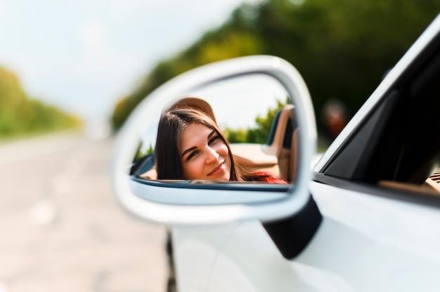Belle femme sur le miroir de voiture