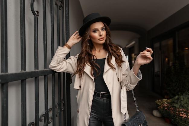 Une belle femme à la mode dans un chapeau élégant avec un manteau classique gris et un sac à main en cuir noir marche dans la rue. style et beauté élégants féminins