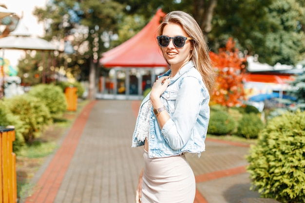 Belle femme à la mode élégante en veste de jeans et lunettes de soleil dans un parc d'attractions
