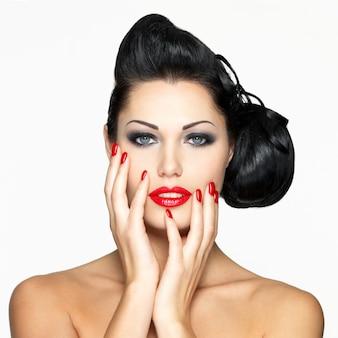 Belle femme de mode avec des lèvres rouges, des ongles et une coiffure créative