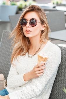 Belle femme à la mode en lunettes de soleil rondes et crème glacée assis dans un café d'été