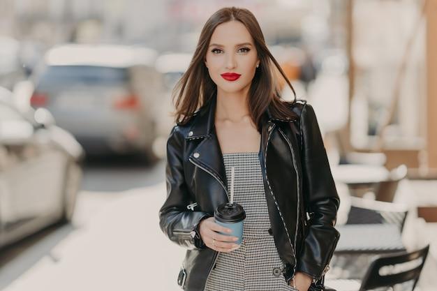 Belle femme à la mode avec le maquillage, les lèvres peintes en rouge vif, porte une veste en cuir noir