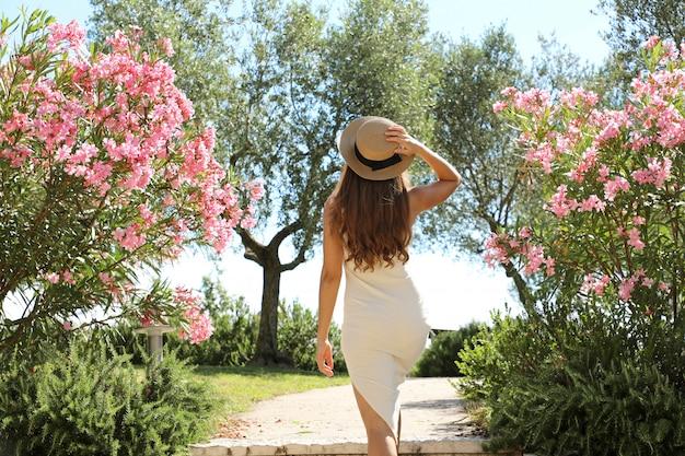 Belle femme de mode sexy entre dans un jardin entre les fleurs à sirmione sur le lac de garde, italie