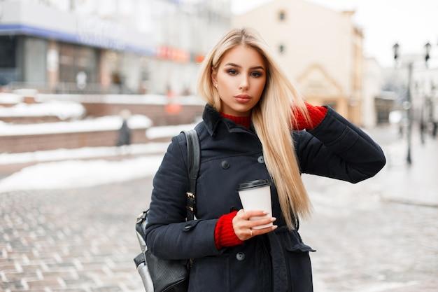 Belle femme à la mode avec une tasse de café dans un manteau à la mode élégant avec un sac voyage dans la ville