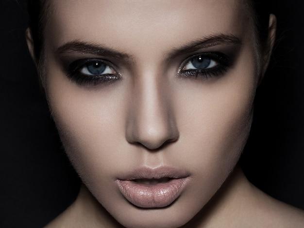 Belle femme modèle maquillage yeux enfumés bouchent sur fond noir