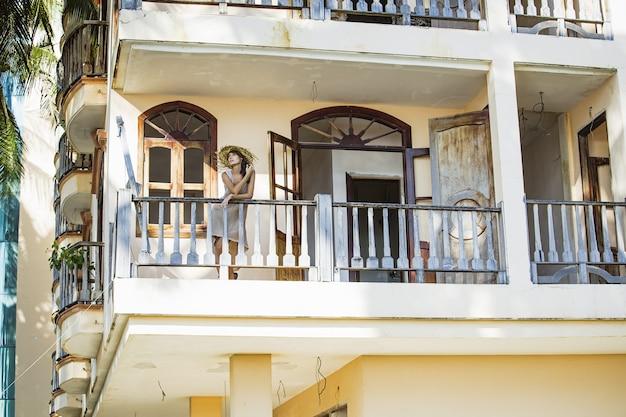 Belle femme modèle à la mode et sexy sur le balcon d'un immeuble ancien en été
