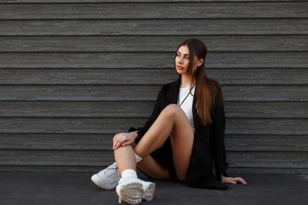 Belle femme modèle sexy en manteau noir avec des chaussures à la mode assis près d'un mur en bois