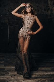 Belle femme modèle sexy en robe de soirée en dentelle de luxe posant dans un masque de carnaval