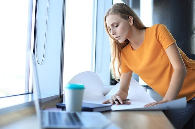 Belle femme moderne écrit quelque chose sur le plan tout en travaillant dans le bureau de création.