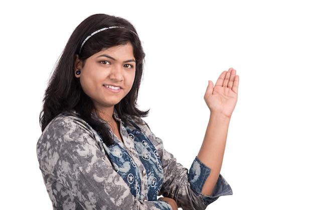Belle femme montrant quelque chose avec un sourire heureux sur un mur blanc.