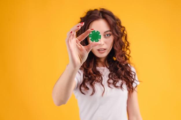 Belle femme montre une puce de poker du casino en ligne isolé sur jaune