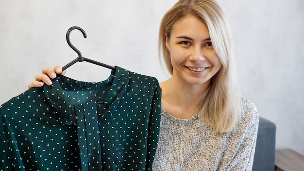Belle femme montre une robe sur un cintre. elle parle de mode et enregistre un blog vidéo