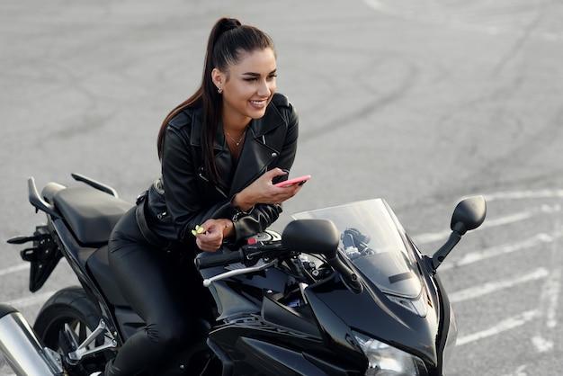 Belle femme motard souriante utilise un smartphone assis sur une moto de sport élégante au parking urbain extérieur.