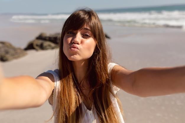 Belle femme moue en regardant la caméra sur la plage au soleil
