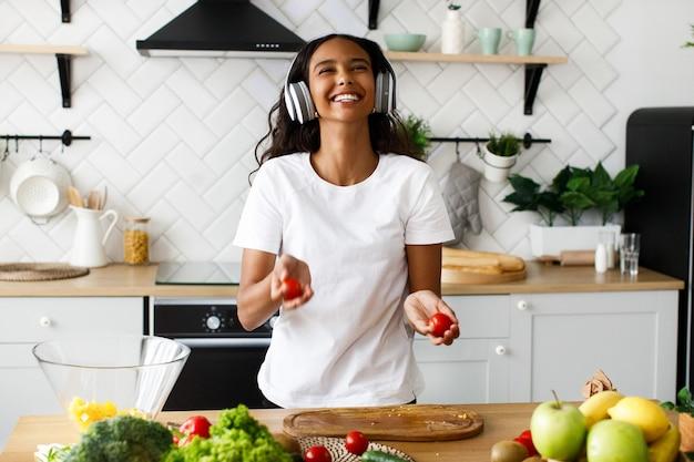 Belle femme mulâtre sourit tient des tomates et écoute quelque chose dans de gros écouteurs près de la table pleine de légumes frais dans la cuisine moderne vêtue d'un t-shirt blanc