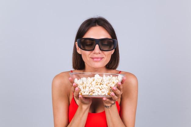 Belle femme sur mur gris dans des lunettes de cinéma 3d avec pop-corn, émotions positives joyeuses et heureuses