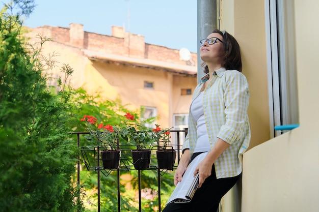 Belle femme mûre dans des vêtements à la maison sur le magazine de lecture de balcon ouvert, espace copie