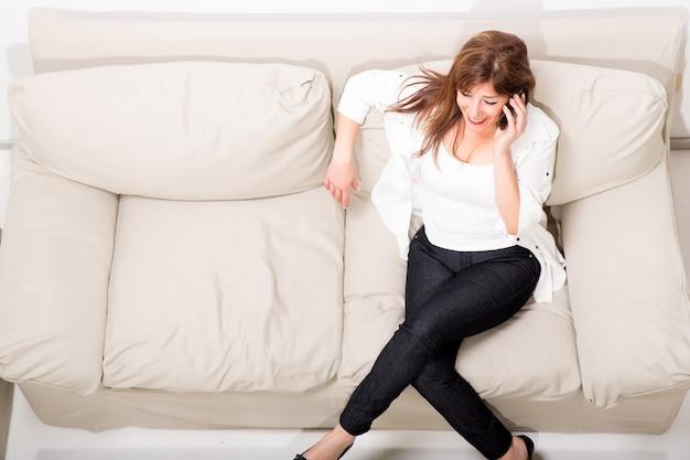Une belle femme mûre parlant sur son téléphone portable sur le canapé