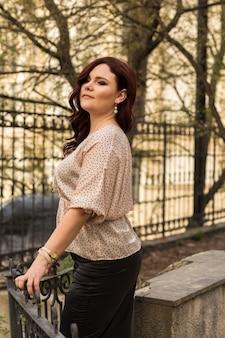 Belle femme mûre portant un chemisier tendance, marchant dans le parc le soir