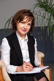 La belle femme mûre, professionnelle, réussie, avec un sourire en costume, assise sur une chaise avec un cahier et un stylo.