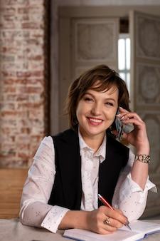 La belle femme mûre, professionnelle, réussie, avec un sourire en costume, assise à une table avec un cahier et un stylo. parler au téléphone