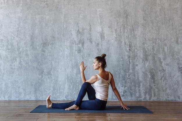 Belle femme musclée fait du sport, pratiquant le yoga sur le tapis