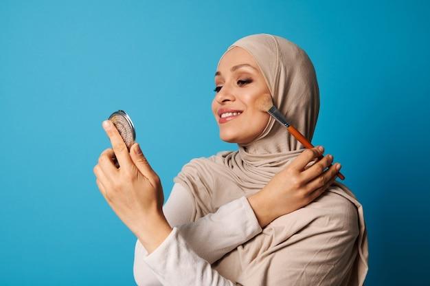 Belle femme musulmane arabe en hijab tient un miroir cosmétique et un pinceau de maquillage et applique le fard à joues sur les pommettes de son visage, isolé