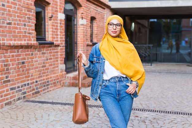 Belle femme musulmane arabe portant le hijab jaune, portrait féminin élégant sur la rue de la ville.