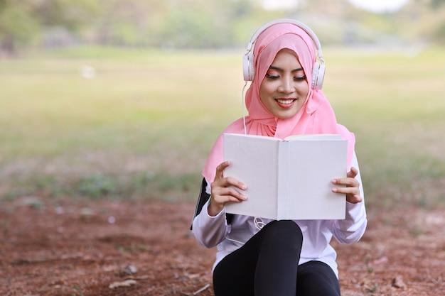 Belle femme musulmane asiatique de remise en forme livre de lecture portant des écouteurs