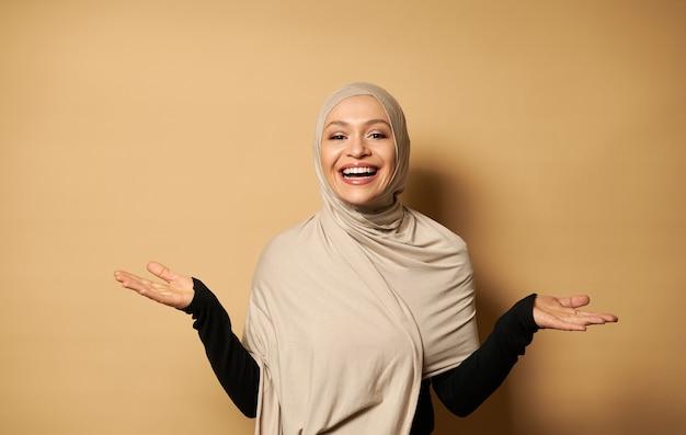 Une belle femme musulmane dans un hijab posant avec ses mains sur le côté sur une surface beige avec espace copie