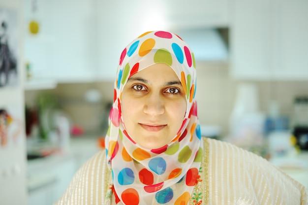 Belle femme musulmane debout dans la cuisine
