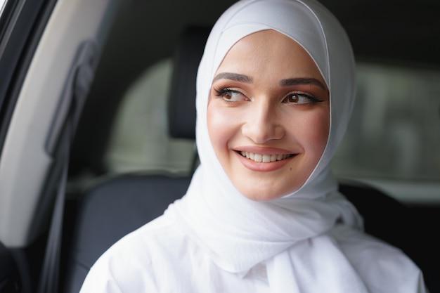 Belle femme musulmane en hijab blanc assis sur le siège arrière d'une voiture de luxe